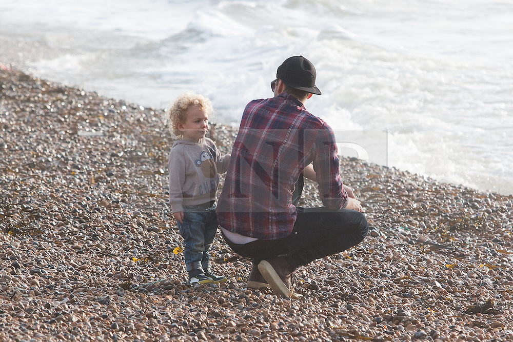 © Licensed to London News Pictures. 19/12/2015. Brighton, UK. Robin MacDonald and 2 year old Marley from Brighton have a great time on the beach as  temperatures are hitting 14C . Today December 19th 2015. Photo credit: Hugo Michiels/LNP