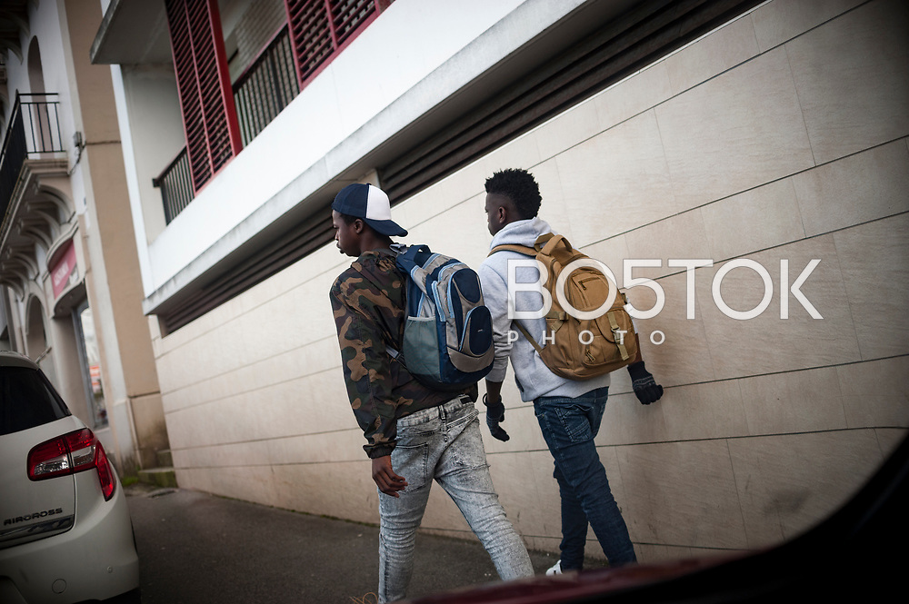 Two young African migrants who crossed the Spanish french border walking along Santiago bridge.  Irun (Basque Country). December 20, 2018. As the number of migrants arriving on the coasts of southern Spain incresead, more and more migrants are heading north to the border city of Irun. (Gari Garaialde / Bostok Photo)