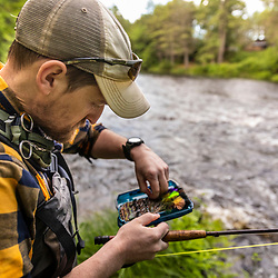 Choosing a fly while fly-fishing on the Crooked River in Otisfield, Maine.