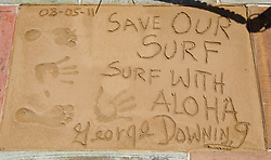 March 6, 2018 - FILE - Big-wave pioneer, surf innovator, mentor and historian George Downing has passed away at 87. Born and raised in Honolulu, Downing surfed Hawaii in the '40s on finless Hot Curls made out of redwood. He was a surfer responsible for many firsts in the sport, and in 1950 he produced the first surfboard with a removable fin. Eight years later he and a handful of other surfers rode 30 foot waves at Makaha, pushing the boundaries of what was believed to be possible at the time. Pictured: Aug. 05, 2011 - Huntington Beach, California, U.S. - George Downing's impressions in concrete at the Surfers' Hall of Fame on Friday in front of Huntington Surf & Sport..(Credit Image: © Mark Rightmire/The Orange County Register/ZUMAPRESS.com)