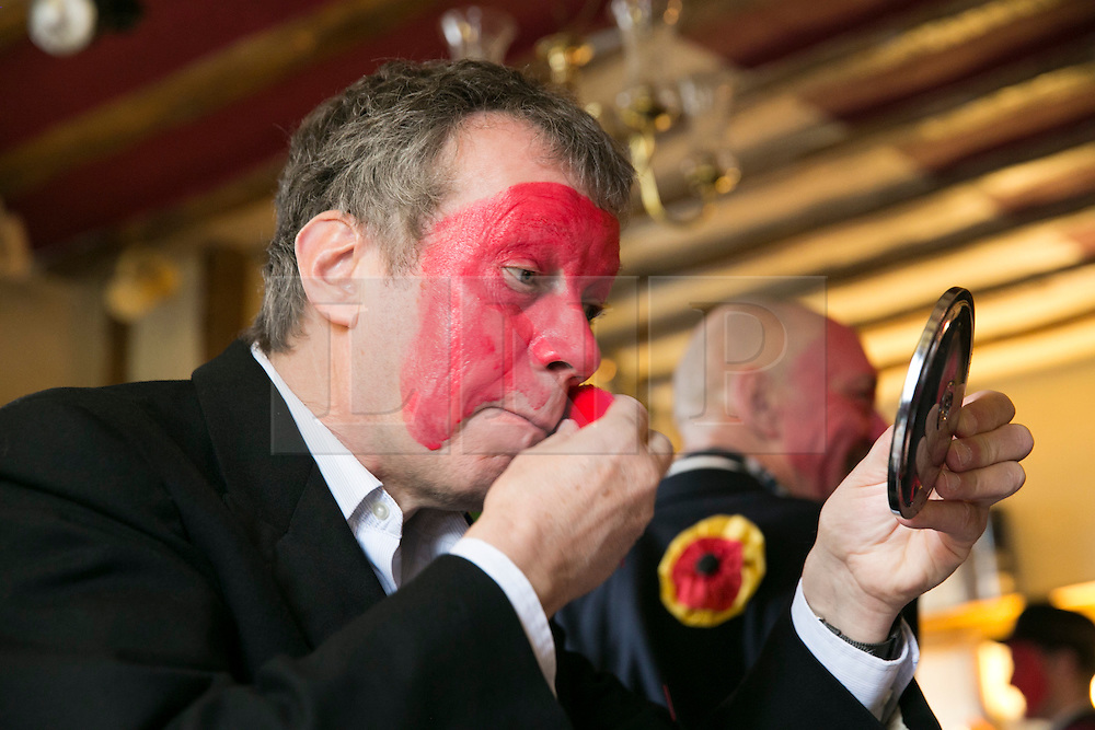 """© Licensed to London News Pictures.10/1/2015.Sharnford, Leicestershire, UK. The annual plough tour by the Hinckley Bullockers took place today. Pictured, Rob Ashton adds the red dye to his face, the tradition stems from when farmers marked their sheep to stop them being stolen. Visiting seven venues around Leicestershire the Bullockers, some with with red painted faces, are seen pulling their decorated plough along the street before stopping to perform traditional dances.<br /> <br /> HISTORY -  On the first Monday after Twelfth Night - Plough Monday - the plough was prepared for the new season, dressed in gaudy ribbons and taken in procession around the villages. In South West Leicestershire the men pulling the plough, who """"raddled"""" their faces, were known as Plough Bullocks and were aided and abetted by dancers who danced dances peculiar to the Eastern Counties. The Plough Bullocks and the Molly Dancers were last seen in this area at the turn of the century in Sapcote.<br />  Traditionally, the Plough Bullockers would stop at public houses, farms and large houses, dance and/or sing and demand recognition in the form of cash donations or drink. If neither was forthcoming the offending landlord's drive was ploughed up. Photo credit : Dave Warren/LNP"""