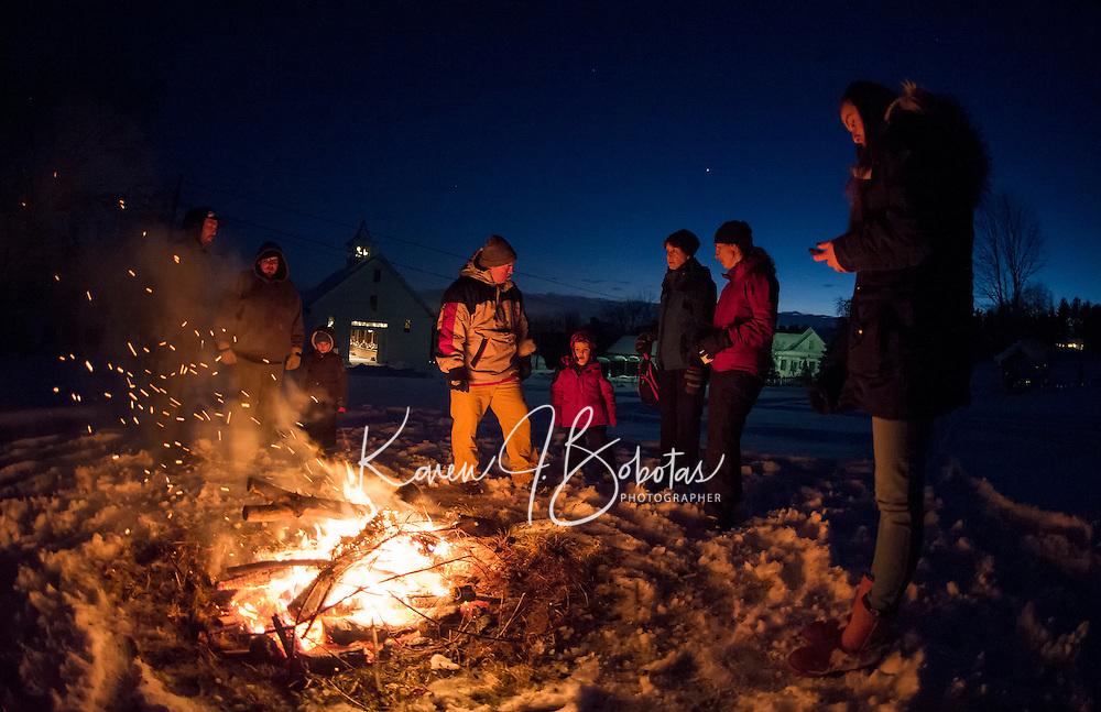 Visitors keep warm gathered around the bonfire during Prescott Farm Lantern Festival held Saturday evening.  (Karen Bobotas/for the Laconia Daily Sun)