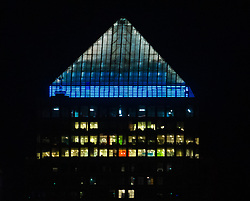 © Licensed to London News Pictures. 24/03/2020. London, UK. The top of One Canada Square is seen illuminated in blue amongst empty offices of banks and financial institutions in London's Canary Wharf financial district this evening. This has been done in recognition and appreciation of National Health Service (NHS) staff working in hospitals across the country during the ongoing COVID-19 coronavirus epidemic. Photo credit: Vickie Flores/LNP