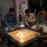 Men play a game of Karom at the local club. The game is somewhat similar to pool and the aim is to shoot the disks into the pockets at the corners of the table.