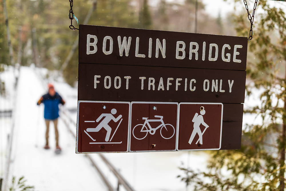 A man snowshoes across the suspension bridge spanning the East Branch of the Penobscot River between Bowlin Camps Lodge and Maine's Katahdin Woods and Waters National Monument.