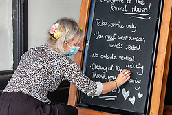 © Licensed to London News Pictures. 24/09/2020. London, UK. A Landlady at a pub in Covent Garden, London writes instructions for customers including a reminder that pubs will close at 10pm tonight as the curfew on hospitality comes into force. The Prime Minister Boris Johnson in his addressed to the Nation this week revealed further tougher Covid restrictions including early closing of pubs and restaurants by 10pm from Thursday and increased fines for not wearing a face mask as a spike in coronavirus cases continues throughout the UK. Photo credit: Alex Lentati/LNP