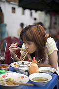 A women eating Pho noodle soup for breakfast at a streetside cafe, Ho Chi Minh City (formerly Saigon), Vietnam