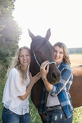 Portrait of two women stroking a horse on meadow and smiling, Bavaria, Germany