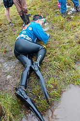 © Licensed to London News Pictures. 30/08/2015. Llanwrtyd Wells, Powys, Wales, UK. A Japanese participant is exhausted after doing the swim.World Bogsnorkelling Championships, conceived 30 years ago in a Welsh pub by landlord Gordon Green, are held every August Bank Holiday at Waen Rhydd Bog. Using unconventional swimming strokes, participants swim two lengths of a 55 metre trench cut through a peat bog wearing snorkel and flippers. The world record was broken in 2014 by 33 year old Kirsty Johnson from Lightwater, Surrey, in a time of 1 min 22.56 secs. Photo credit: Graham M. Lawrence/LNP