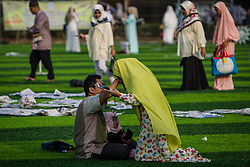 February 14, 2013 - Central Jakarta, Jakarta, Indonesia - Wife kiss her husband hands after Eid Al-Fitr prayer on plastic grass at futsal stadium on June 15, 2018 in Jakarta, Indonesia. Muslims around the world are celebrating Eid al-Fitr, the three day festival marking the end of the Muslim holy month of Ramadan, it will be observed on 15th or 16th of June depending on the lunar calendar. Eid al-Fitr is one of the two major holidays in Islam. (Credit Image: © Afriadi Hikmal via ZUMA Wire)
