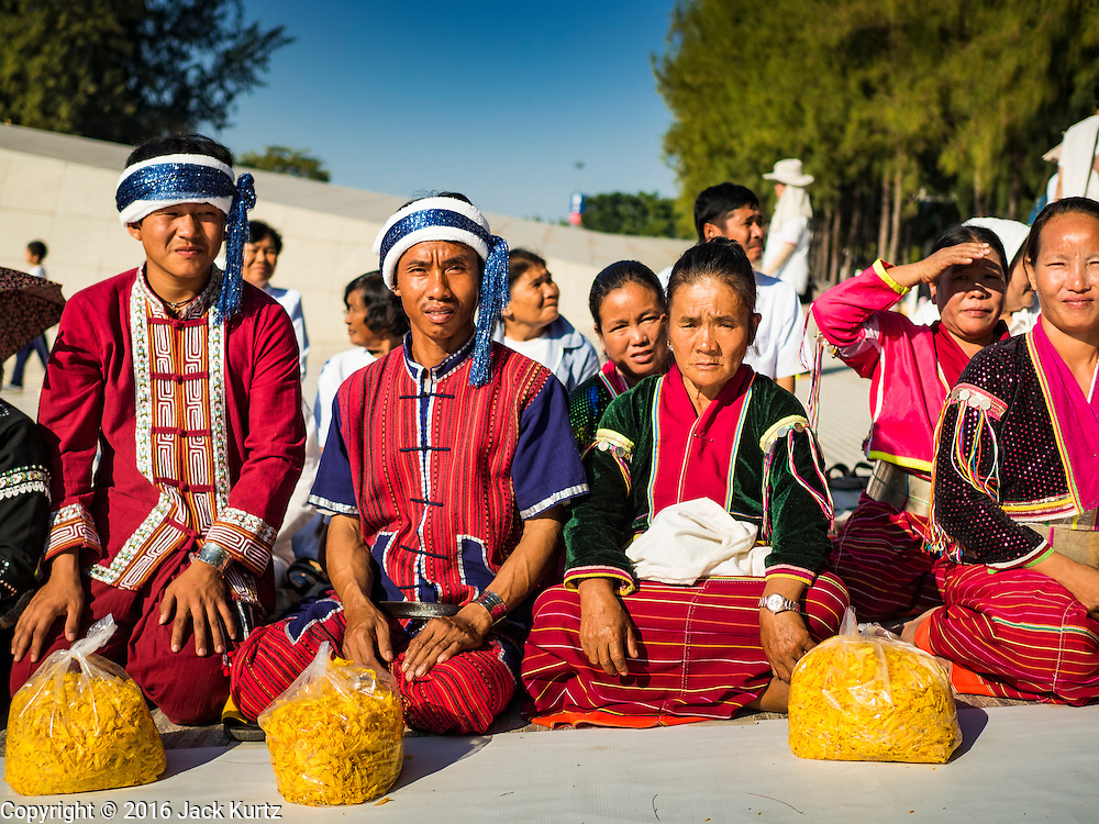 """02 JANUARY 2016 - KHLONG LUANG, PATHUM THANI, THAILAND:  Hill tribe people from northern Thailand, on the border with Myanmar, wait for the start of a mass pilgrimage of Buddhist monks at Wat Phra Dhammakaya on the first day of the 5th annual Dhammachai Dhutanaga (a dhutanga is a """"wandering"""" and translated as pilgrimage). More than 1,300 monks are participating pilgrimage through central Thailand. The purpose of the pilgrimage is to pay homage to the Buddha, preserve Buddhist culture, welcome the new year, and """"develop virtuous Buddhist youth leaders."""" Wat Phra Dhammakaya is the largest Buddhist temple in Thailand and the center of the Dhammakaya movement, a Buddhist sect founded in the 1970s. The monks are using busses on some parts of the pilgrimage this year after complaints about traffic jams caused by the monks walking along main highways.         PHOTO BY JACK KURTZ"""