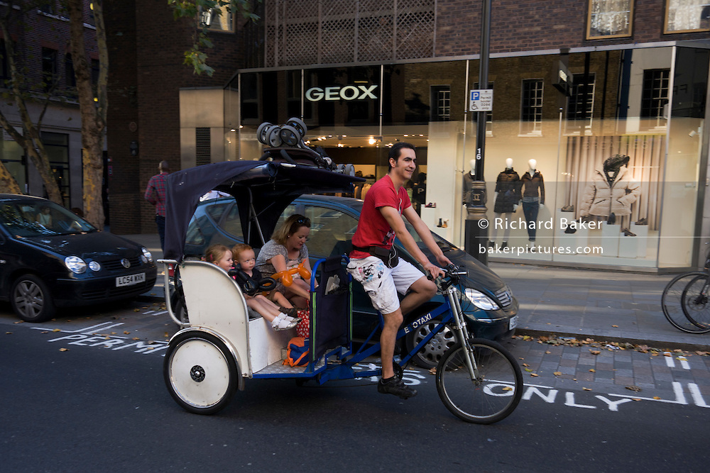 A mother sits alongside her young children whilst riding in a central London rickshaw taxi with the kids' pushchair on the roof.