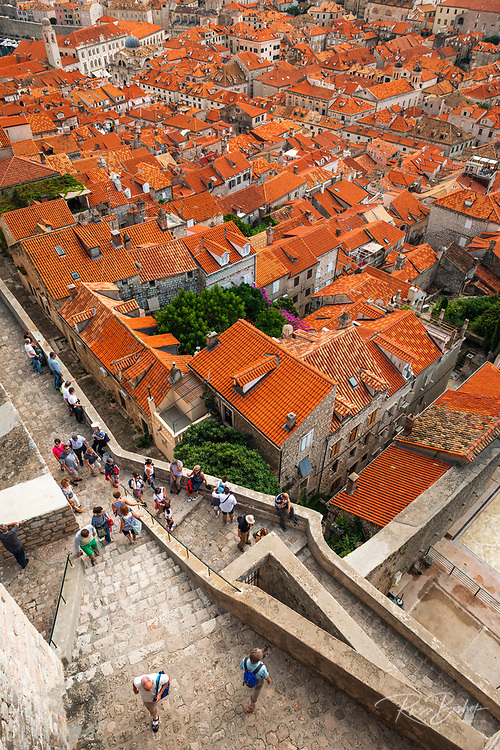 Red tile roofs and tourists on the ancient city wall above old town Dubrovnik, Dalmatian Coast, Croatia