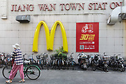 Pedestrians walk past a large McDonalds golden arches sign in Shanghai, China, on Sunday, August 7, 2016.