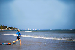 Boy running with surfboard into sea, Mauritius