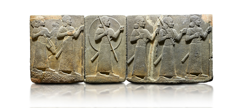 Hittite relief sculpted orthostat stone panel of Royal Buttress Basalt, Karkamıs, (Kargamıs), Carchemish (Karkemish), 900-700 B.C. Warriors. Anatolian Civilisations Museum, Ankara, Turkey.<br /> <br /> Right panel - Three figures each with a long dress, a thick belt and curly hair. The figure in front holds a spear with a broken tip in his left hand and a leafy branch in his right hand. The figure in the middle made his left hand a fist, and he carries a tool with his right hand at the level of his head. They are followed with a figure holding a sceptre in his left hand. All three have each a long sword at their waist. <br /> <br /> Against a white background. .<br />  <br /> If you prefer to buy from our ALAMY STOCK LIBRARY page at https://www.alamy.com/portfolio/paul-williams-funkystock/hittite-art-antiquities.html  - Type  Karkamıs in LOWER SEARCH WITHIN GALLERY box. Refine search by adding background colour, place, museum etc<br /> <br /> Visit our HITTITE PHOTO COLLECTIONS for more photos to download or buy as wall art prints https://funkystock.photoshelter.com/gallery-collection/The-Hittites-Art-Artefacts-Antiquities-Historic-Sites-Pictures-Images-of/C0000NUBSMhSc3Oo .