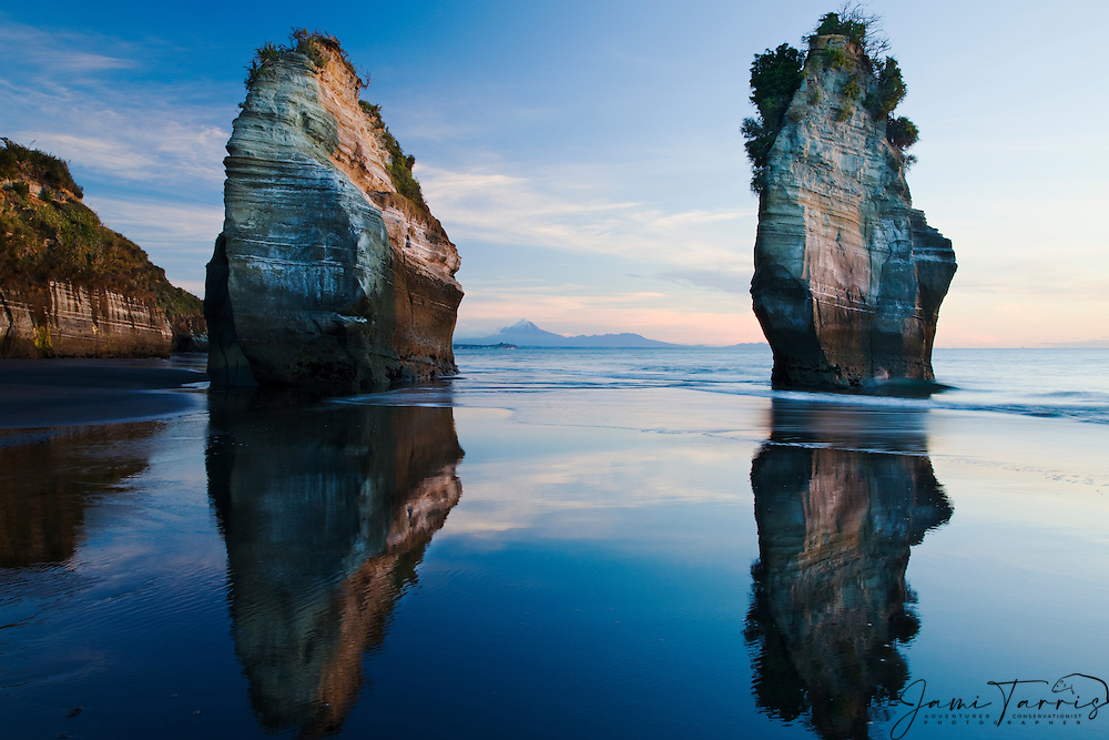 On the west coast along the Tasman Sea are the majestic rock pinnacles of the 'Three Sisters' of which two are standing today. A snow capped Mount Egmont sits behind the Three Sisters,  North Island, New Zealand