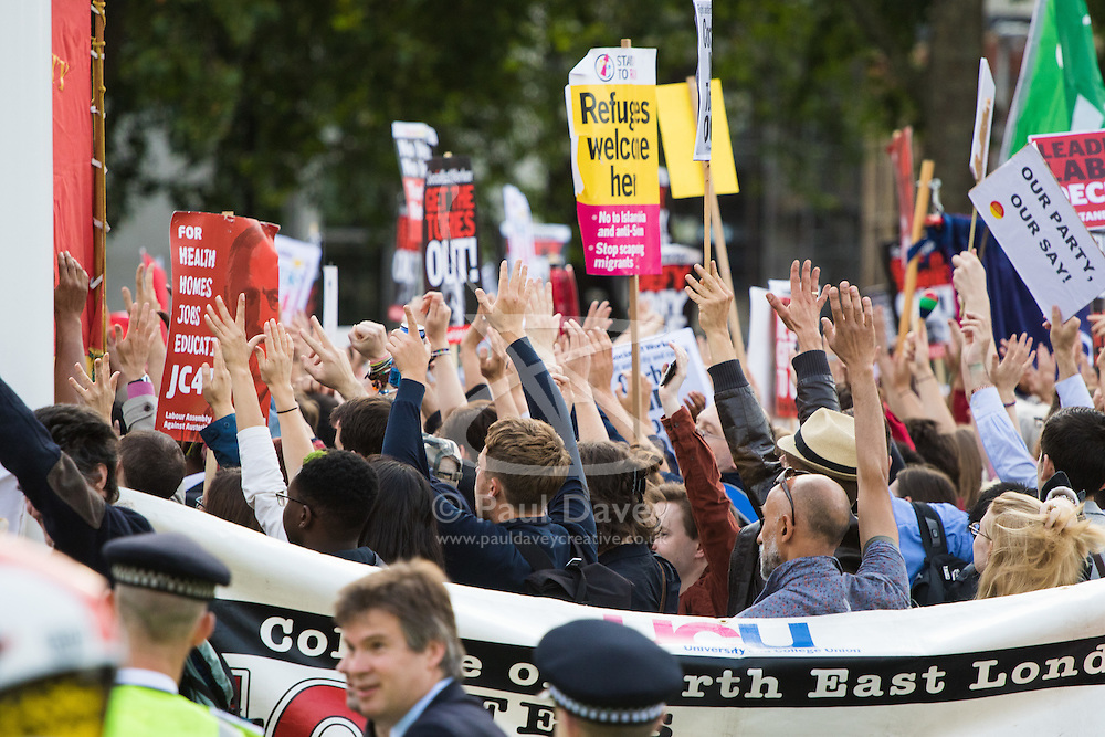 Parliament Square, Westminster, London, June 27th 2016. Thousands of Labour's Momentum members and their supporters gather in Parliament Square in a display of support for embattled Labour Leader Jeremy Corbyn as he suffers numerous calls for his resignation by party members, saying he has does not have the authority to lead the divided party, following his less than emphatic support for Remain in the EU referendum. PICTURED: The crowd raises their hands in a show of support for Jeremy Corbyn.