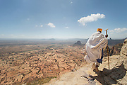 Priest walking the rock edge path to the Mariam Korkor Church. Tigray, Ethiopia, Horn of Africa
