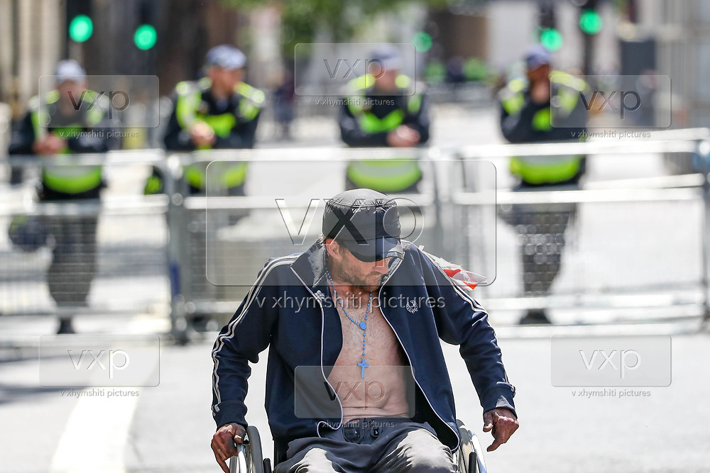 A disabled man rides around the British police officers in riot gear who formed a cordon near Downing Street in central London, as members of far-right groups gather to counter-protest against a Black Lives Matter demonstration, Saturday, June 13, 2020. British police have imposed strict restrictions on groups planning to protest in London Saturday in a bid to avoid violent clashes between protesters from the Black Lives Matter movement, as well as far-right groups. (Photo/ Vudi Xhymshiti)