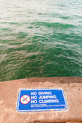 A sign warns people not to dive, jump, or climb on the pier in Waikiki.
