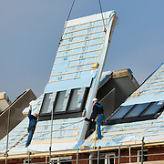 Nederland Barendrecht 27 januari 2009 20090127 Foto: David Rozing ..Bouwvakkers plaatsen prefab dakdelen op nieuwbouw woningen .Prefab roof top is being placed on house ..Foto David Rozing