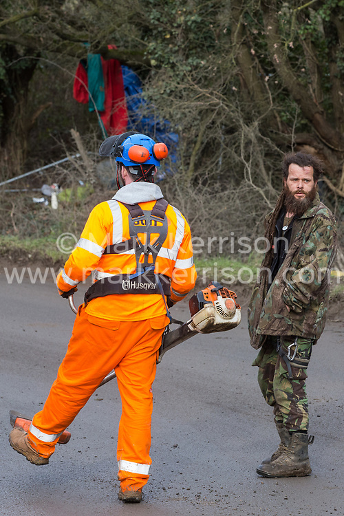 Harefield, UK. 8 February, 2020. An environmental activist monitors HS2 engineers with a chainsaw on Harvil Road in the Colne Valley. HS2 had scheduled tree felling work in the area for the high-speed rail project, implementing road and rail closures for this purpose, but were prevented from any tree felling by action from the environmental activists.
