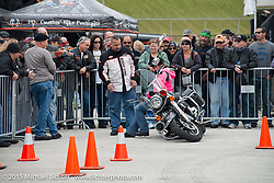 Milwaukee policeman and Harley-Davidson employee George Petropouls teaches Renee Cabrera of Tampa, FL how easy it is to pick up a bike that has fallen over at the Harley-Davidson display at Daytona International Speedway on the first day of Daytona Beach Bike Week 2015. FL, USA. Saturday, March 7, 2015.  Photography ©2015 Michael Lichter.