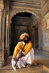 India, Rajasthan, Jaisalmer. Man playing Nad (flute) at Salim Singh-ki Haveli, 17th c. carved sandstone mansion