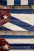 Ceramic Cuban flags, artworks hanging on a wall in an artists studio.