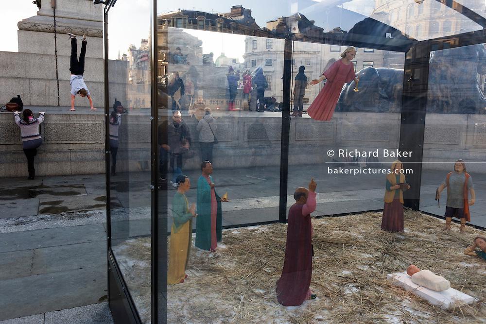 A holy nativity scene titled Christmas Crib by the artist Tomoaki Suzuki with background acrobat in London's Trafalgar Square