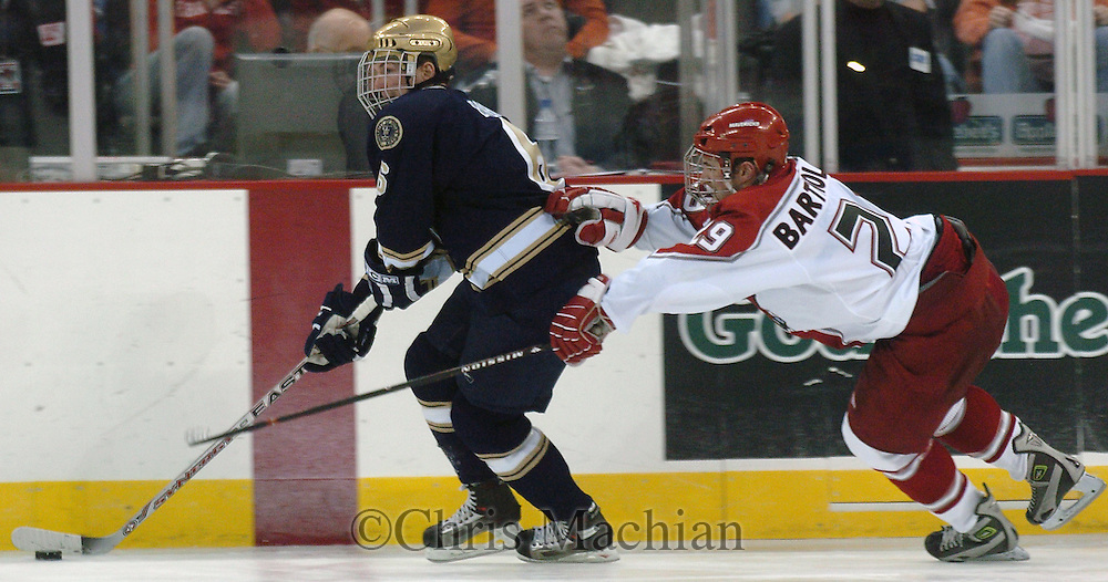 11/25/06 Omaha, NE University of Nebraska at Omaha' Adam Bartholomay tries to steal the puck from Notre Dame's Noah Babin Saturday night at the Qwest Center Omaha..(Chris Machian/Prairie Pixel Group)..