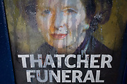 The face of ex-British Prime Minister Margaret Thatcher printed on a newspaper souvenir issue is rain streaked the day after her ceremonial funeral was held in central London. Afforded a ceremonial funeral with military honours, not seen since the death of Winston Churchill in 1965, family and 2,000 VIP guests (incl Queen Elizabeth) await her cortege. Margaret Hilda Thatcher, Baroness Thatcher (1925 - 2013) was a British politician who was the Prime Minister of the United Kingdom from 1979 to 1990 and the Leader of the Conservative Party from 1975 to 1990, the longest-serving British Prime Minister of the 20th century and the only woman to have held the office to date.