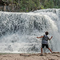 A youngster skips rocks below Ouzel Falls near Big Sky, Montana.