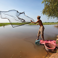 This man threw his cast net a few times over the water, before he could catch some bigger fish.