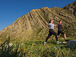Man and woman running on single trail on cliff of Getxo