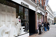 Shopping queue outside the Chanel store in the upmarket area of Knightsbridge on 14th April 2021 in London, United Kingdom. Knightsbridge is one of the principal areas for exclusive, luxury goods in West London. It is known as a district where the rich and wealthy shop, mostly for high end fashion and jewellery.