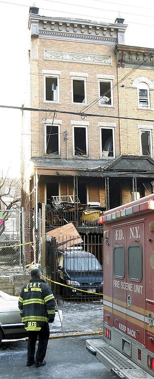 A New York City fire marshall stands outside of a house where 9 people were killed, 8 of them children, in a fire over night in the Bronx, New York on Thursday 08 March 2007.