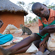 Liliosa (in blue), 16, eats cornmeal in Masvingo Province, Zimbabwe, while her sister Letwin, 13, feeds Liliosa's baby. Letwin is born HIV positive. <br /> <br /> Drought in southern Africa is devastating communities in Zimbabwe, leaving 4 million people urgently in need of food aid. The government declared a state of emergency,. <br /> <br /> Here in Masvingo Province, the country's hardest hit province, vegetation has wilted, livestock is dying, and people are at serious risk of famine. <br /> <br /> Pictures shot by Justin Jin