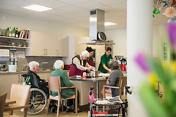 Nurse preparing food with senior inhabitants in rest home