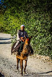 A berber man on horse back makes his way along the track through the M'Goun Gorge n M'goun Amazigh territory, Morocco<br /> <br /> (c) Andrew Wilson   Edinburgh Elite media