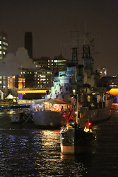 """© Licensed to London News Pictures. 15/09/2013. A cloud of smoke rises above HMS Belfast after a gun is fired as part of the Ships' Opera event. """"1513: A Ships' Opera"""" by Richard Wilson and Zatorski + Zatorski was a centrepiece event in the Mayor of London's Thames Festival on Saturday night. The spectacular event brought together an armada of historic vessels in the Upper Pool of the Thames with a soundtrack of bells, whistles, horns and even gunfire from HMS Belfast. (Online usage can be accompanied by this video also: http://youtu.be/Lzj8DDBD3Kk) Credit : Rob Powell/LNP"""