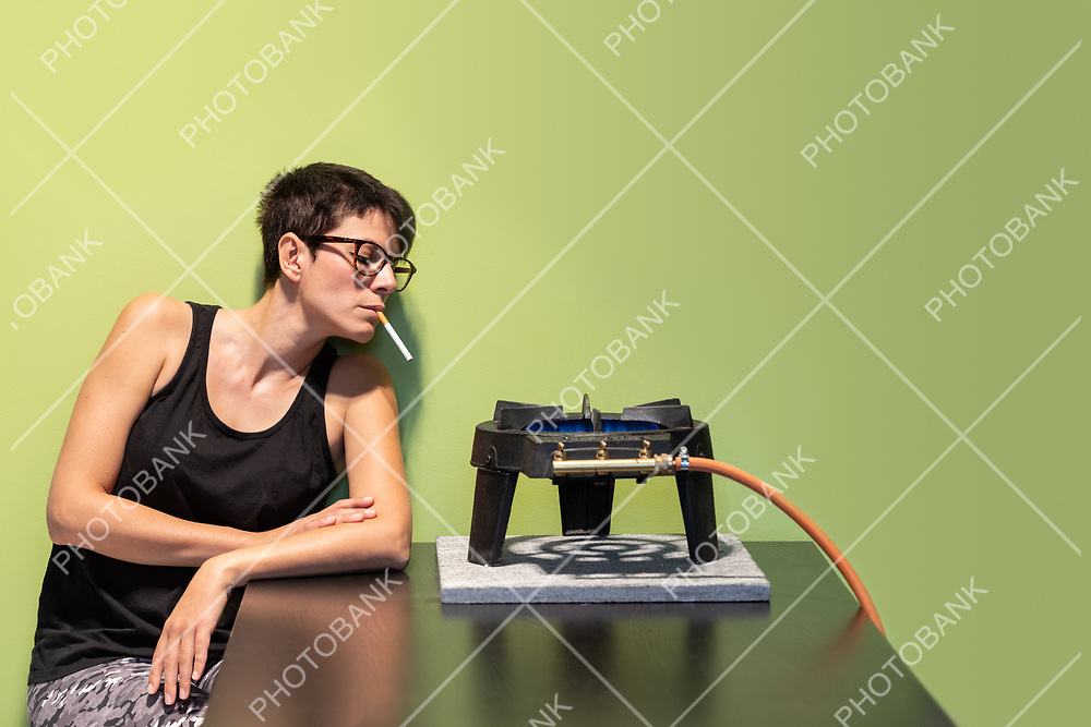 Young woman with black tank top lights cigarette with gas stove. Green background