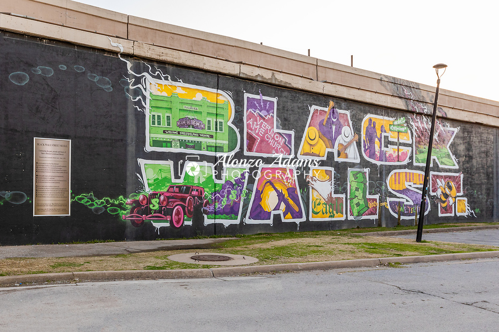 A Black Wall Street mural painted on the wall of I-244 in Tulsa, Oklahoma in the historic Greenwood District where the 1921 Tulsa race massacre took place. Photo copyright © 2021 Alonzo J. Adams.