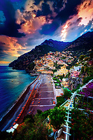 """""""Dramatic sunset over Positano""""…<br /> <br /> After an exhilarating drive along the high cliffs on the Amalfi coast from Sorrento down to Positano, I found myself in sensory overload with its beauty and photogenic appeal.  After circling around the entire village and its cliffside three times on Positano's only street, which was a single lane winding down from the top and back up and over to where I began, I finally found the parking garage by the hotel, about 2/3rds up the facing village in this image.  The climb down the winding road and steep staircases made for quite a workout in the hot late May sun.  Reaching the beach and marina, I forgot about my exhaustion and could not capture enough of Positano's plush beauty; however, the large amount of tourists and bright sun did not allow for ideal conditions.  Walking the length of the beach, I found a very, very steep staircase leading straight up to a large veranda at the Albergo California.  Taking an exhaustive seat on a plush lounge chair with a perfect view to watch the sunset behind the Amalfi Cliffs, I was taken back by a pleasant Italian (Positano) waiter from the hotel offering a towel, ice water, and drinks for the evening.  I expressed that I was not staying at the hotel, but he didn't seem to mind and proceeded to educate me on the culture of this historic resort village.  The sunset was being coy and didn't appear to cooperate, but during opportune moments it mystified the ominous clouds, and contributed just enough light and color to satisfy a weary photographer."""