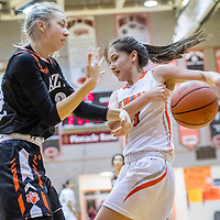Aztec Tiger Reigan Weaver (32), left, wrestles a ball free from Gallup Bengal Ashley Antone (1)  at Gallup High School Saturday.