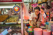 "05 OCTOBER 2012 - BANGKOK, THAILAND: A street vendor works at her cart in the Chinatown section of Bangkok, Thailand. Thailand in general, and Bangkok in particular, has a vibrant tradition of street food and ""eating on the run."" In recent years, Bangkok's street food has become something of an international landmark and is being written about in glossy travel magazines and in the pages of the New York Times.       PHOTO BY JACK KURTZ"