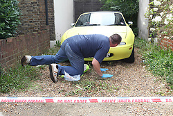 """© Licensed to London News Pictures. 11/08/2011. Harlington. London, U.K. Police examine a yellow car at the scene. Police are treating the deaths of a man and woman in their 20s as """"unexplained"""" after their bodies were discovered in a house. Scotland Yard was called to the property in Harlington, west London, after being alerted by someone concerned about the welfare of the pair yesterday. Photo credit : Rob Bourne/LNP"""
