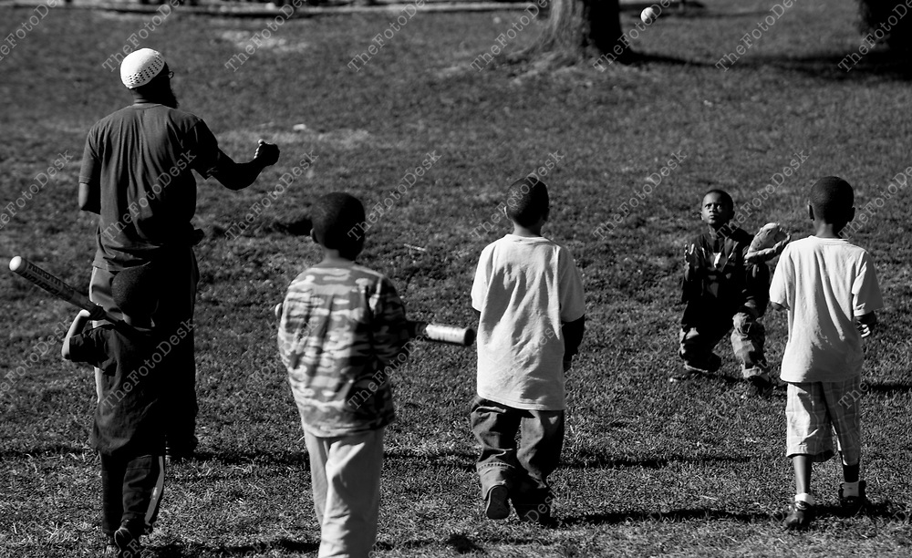 An African American male father with playing baseball with boys and sons. (Brian Branch Price)