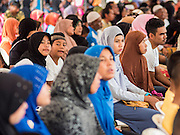14 JUNE 2015 - NARATHIWAT, NARATHIWAT, THAILAND: Thai Muslims wait for a food distribution event to start in Narathiwat. The food distribution is held before Ramadan, which starts June 18. The annual food distribution event is organized by the Southern Peace Media Club, a group of Thai journalists who work in the southern provinces of Pattani, Narathiwat and Yala. An insurgency pitting Muslim extremists against the Thai government has rocked Thailand's southern three provinces since 2001. More than 6,000 people have been killed in the sectarian violence.    PHOTO BY JACK KURTZ